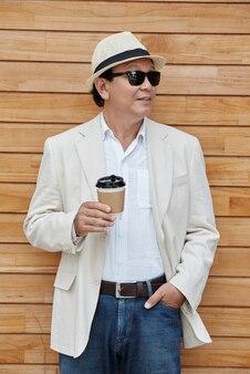 Przystojny dojrzały azjata z kawą na wynos