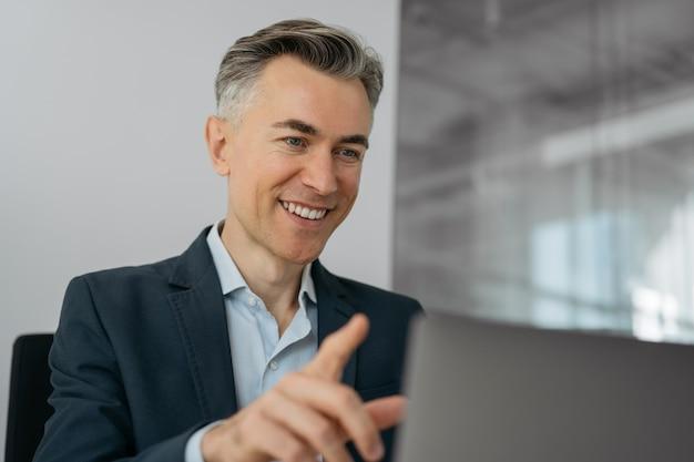 Przystojny dojrzały biznesmen komunikacji online, nawiązywanie połączenia wideo pracującego w domu. koncepcja wideokonferencji