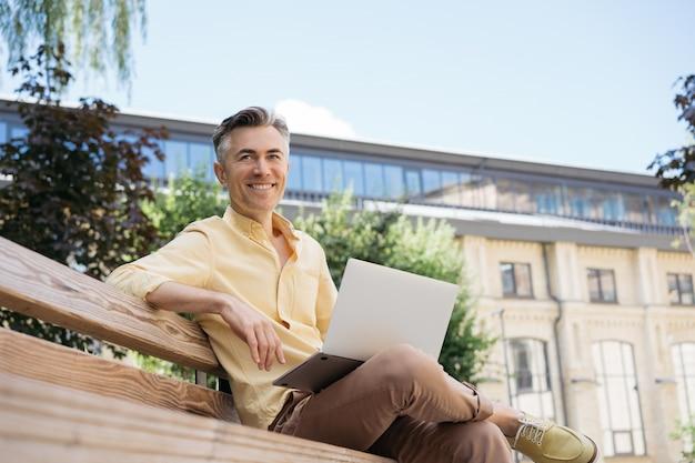 Przystojny dojrzały biznesmen przy użyciu, planowanie uruchomienia, siedząc na zewnątrz