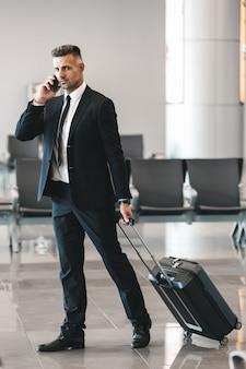 Przystojny dojrzały biznesmen rozmawia przez telefon komórkowy