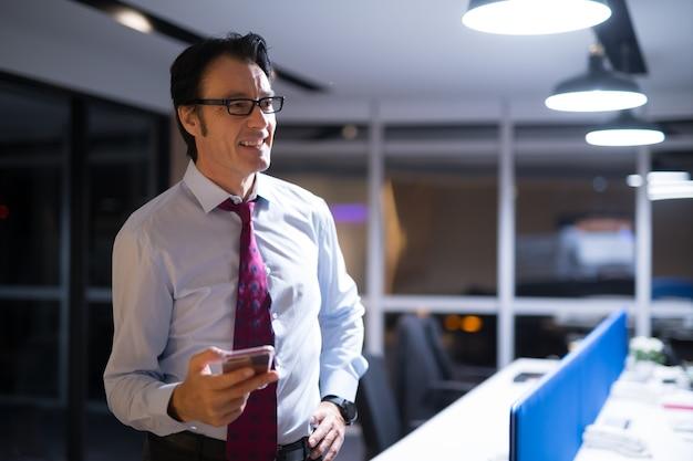 Przystojny dojrzały biznesmen siedzi i pracuje w biurze w nocy