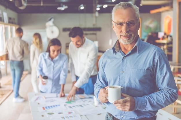 Przystojny dojrzały biznesmen trzyma filiżankę kawy