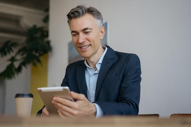 Przystojny dojrzały biznesmen za pomocą cyfrowego tabletu do czytania wiadomości, pracujący online w nowoczesnym biurze