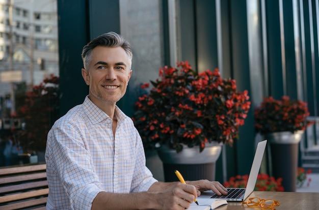 Przystojny dojrzały biznesmen za pomocą laptopa, robienie notatek, planowanie uruchomienia