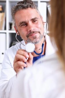 Przystojny dojrzały lekarz trzymać w głowie stetoskop ramię