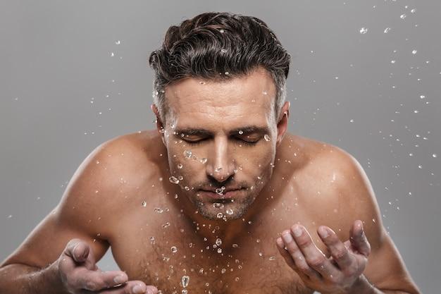 Przystojny dojrzały mężczyzna do mycia twarzy.