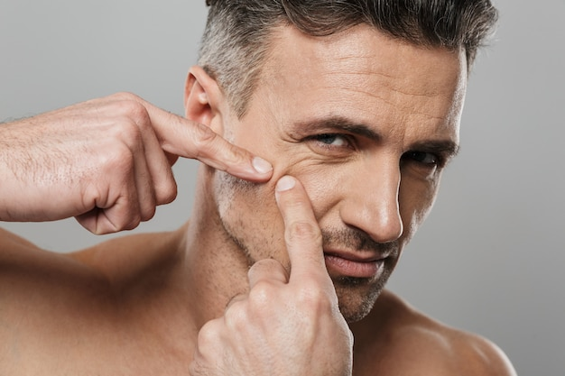Przystojny dojrzały mężczyzna nagi dba o swoją skórę wyciska pryszcz.