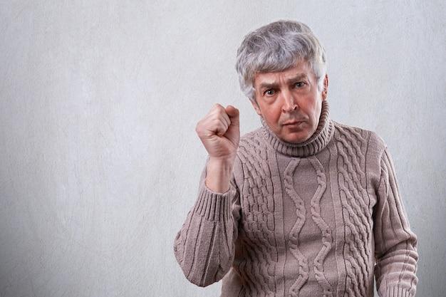 Przystojny dojrzały mężczyzna pokazujący pięść, będąc wściekły i rozdrażniony. starszy mężczyzna ze zmarszczkami, pokazujący swoje niezadowolenie z gestu