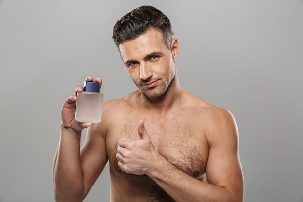 Przystojny dojrzały mężczyzna trzyma perfumy. patrząc na aparat z kciukami do góry.