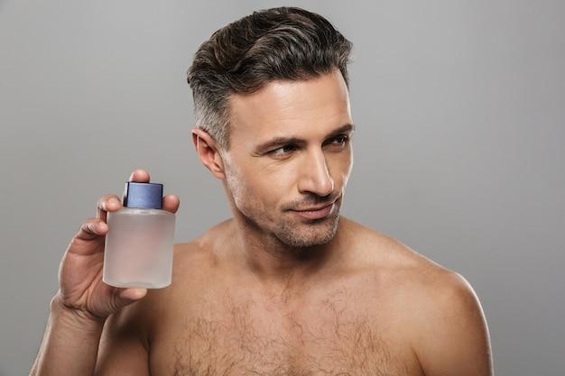 Przystojny dojrzały mężczyzna trzyma perfumy. patrząc na bok.