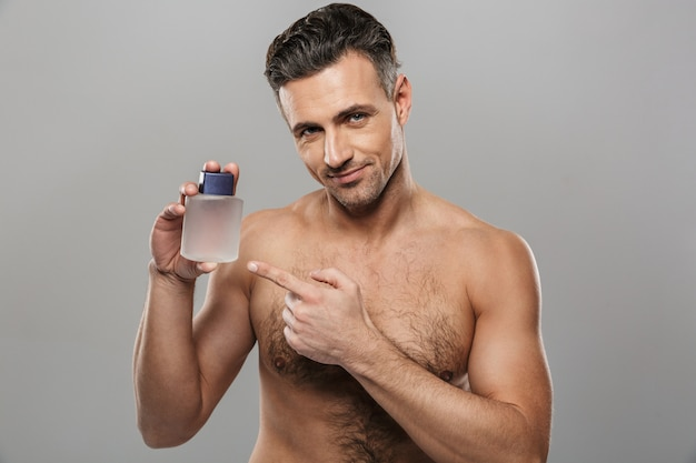 Przystojny dojrzały mężczyzna trzyma perfumy.