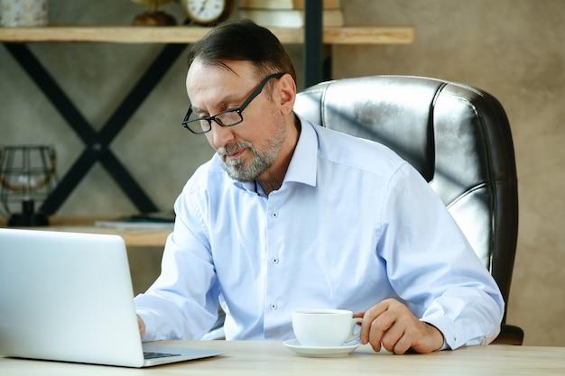 Przystojny dojrzały mężczyzna używa laptopa w domu