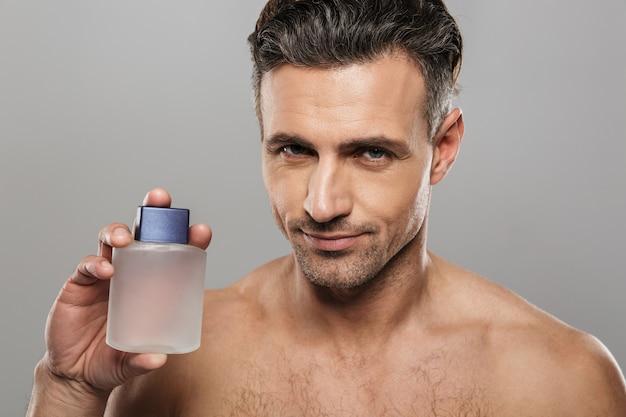 Przystojny dojrzały mężczyzna wesoły trzymając perfumy.