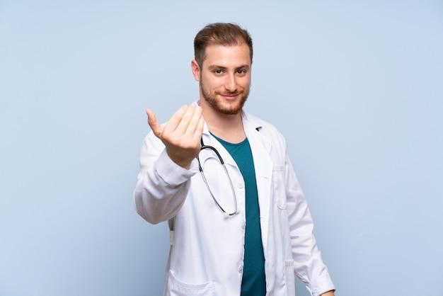 Przystojny doktorski mężczyzna nad błękita ścianą zaprasza przychodzić z ręką. szczęśliwy, że przyszedłeś