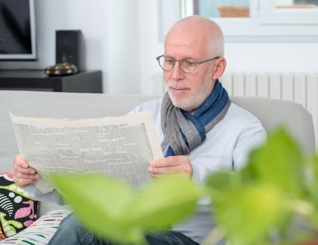 Przystojny dorośleć mężczyzna czyta newpaper na kanapie