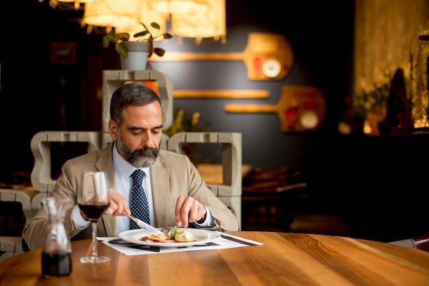 Przystojny dorośleć mężczyzna pije czerwone wino podczas lunchu