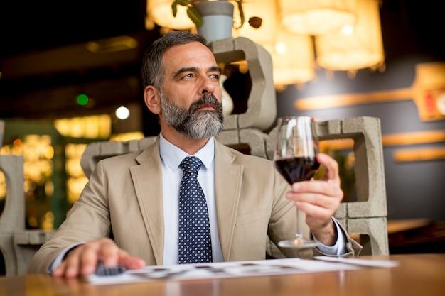 Przystojny dorośleć mężczyzna pije szkło czerwone wino w restauraci