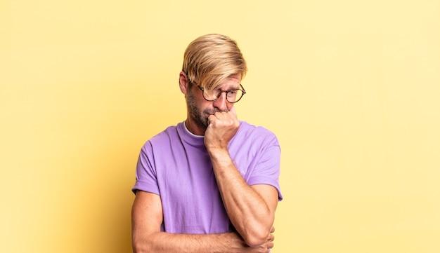 Przystojny, dorosły blondyn, czujący się poważny, zamyślony i zatroskany, wpatrujący się w bok z dłonią przyciśniętą do podbródka