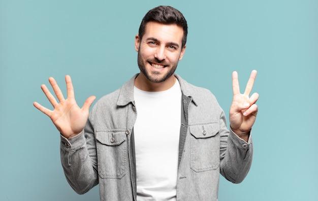 Przystojny dorosły blondyn uśmiechający się i wyglądający przyjaźnie, pokazujący numer siedem lub siódmy z ręką do przodu, odliczający w dół