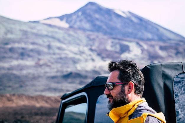 Przystojny dorosły kaukaski mężczyzna z brodą i okularami przeciwsłonecznymi i górą - podróż przygoda ludzie odkryty koncepcja z samochodem terenowym i sprzętem - aktywny styl życia