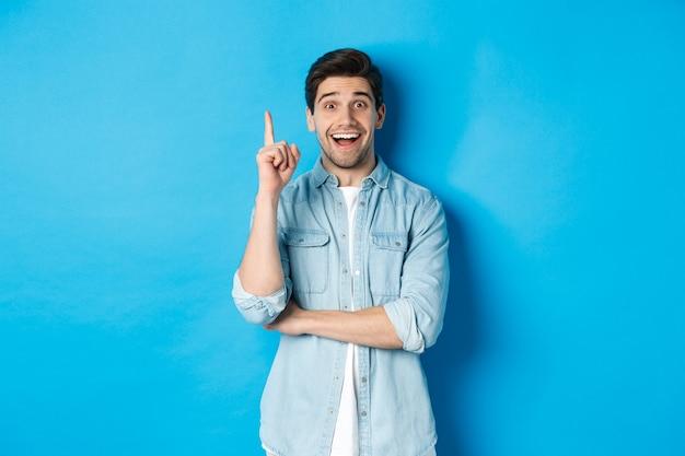 Przystojny dorosły mężczyzna mający pomysł, podnosząc palec i uśmiechając się podekscytowany, znalazł rozwiązanie, stojąc przed niebieską ścianą