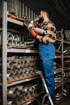 Przystojny dorosły mężczyzna pracujący w magazynie części zamiennych do samochodów i ciężarówek.
