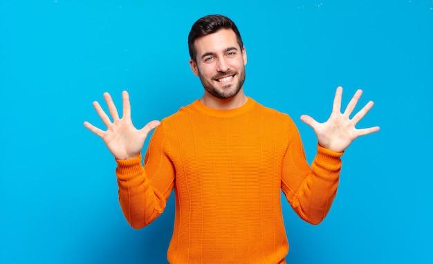 Przystojny dorosły mężczyzna uśmiechnięty i wyglądający przyjaźnie, pokazujący numer dziesięć lub dziesiątą ręką do przodu, odliczający w dół