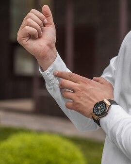 Przystojny dorosły mężczyzna zapina nadgarstek białej koszuli
