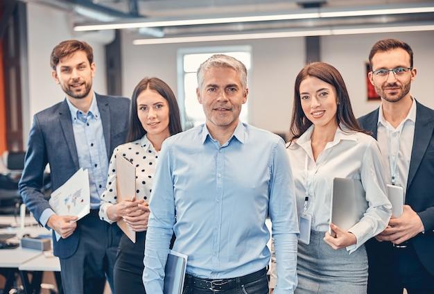 Przystojny dorosły mężczyzna ze swoim profesjonalnym zespołem w biurze