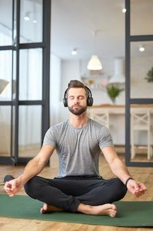 Przystojny dżentelmen w słuchawkach bezprzewodowych, cieszący się relaksującą muzyką i wykonujący ćwiczenia medytacyjne, siedząc na macie do jogi w domu
