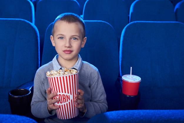 Przystojny dzieciak patrzeje kamerę, pozuje w kinie.