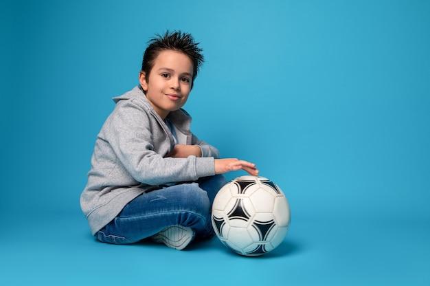 Przystojny dziecko siedzi w pobliżu piłki nożnej