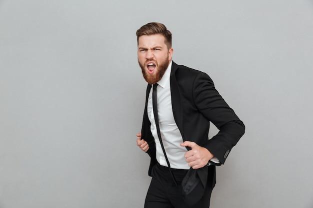Przystojny elegancki biznesmen w kostiumu pozuje podczas gdy stojący