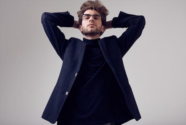 Przystojny elegancki mężczyzna z kręconymi włosami na sobie garnitur i okulary