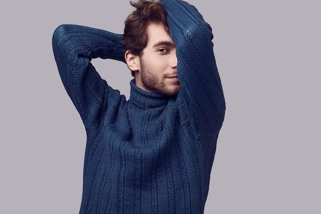 Przystojny elegancki mężczyzna z kręconymi włosami w niebieskim swetrze