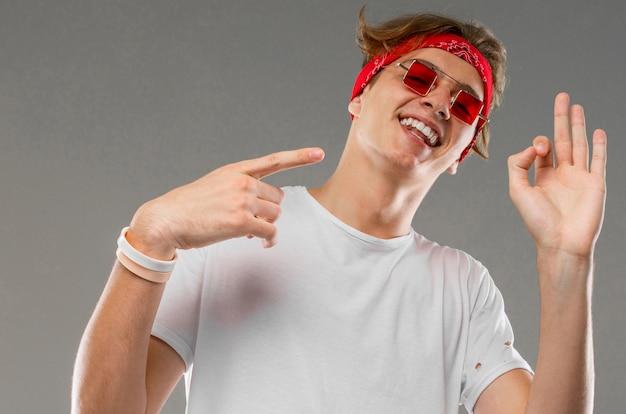 Przystojny emocjonalny nastolatek chłopak pozowanie studio przeciwko szary, facet w szary t-shirt i czerwone okulary gesty ok
