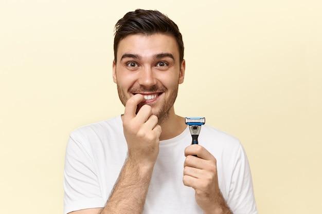 Przystojny emocjonalny zabawny młody mężczyzna z włosia pozowanie na białym tle z kijem do golenia i obgryzaniem paznokci