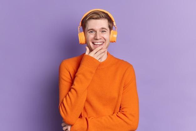 Przystojny europejczyk uśmiecha się radośnie wyraża pozytywne emocje słucha ścieżki dźwiękowej przez słuchawki stereo ubrany w pomarańczowy sweter