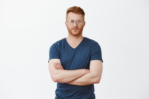 Przystojny europejski biznesmen z rudymi włosami i włosiem w chłodnych przezroczystych okularach, trzymający kciuki na piersi