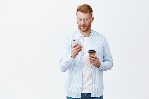 Przystojny europejski rudy mężczyzna z włosiem w okularach i koszuli sprawdzający czas w smartfonie, stojąc nad szarą ścianą czekając na przyjaciela, pijąc kawę, patrząc na ekran telefonu komórkowego, uśmiechając się