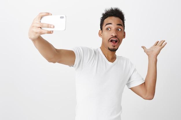 Przystojny facet afroamerykanin pokazujący coś podczas robienia selfie