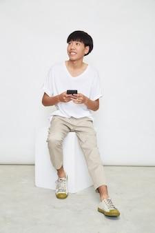 Przystojny facet azjatyckich siedzieć i używać telefonu na białym tle na białej powierzchni. skopiuj miejsce