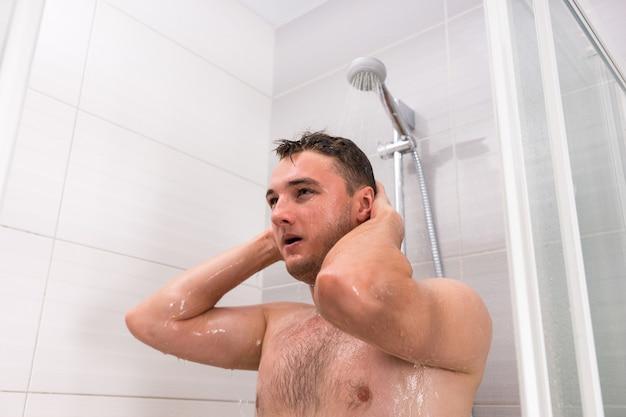 Przystojny facet biorący prysznic w nowoczesnej, wyłożonej kafelkami łazience