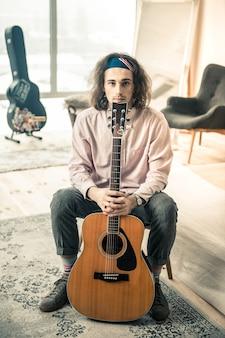 Przystojny facet. długowłosy spokojny mężczyzna siedzący na krześle z gitarą akustyczną w połączonych rękach