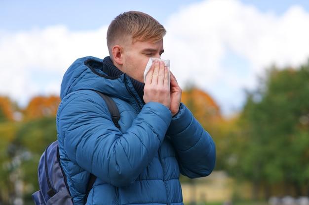 Przystojny facet dmuchający nos w papierową chusteczkę na zewnątrz na naturalnym złotym jesiennym tle