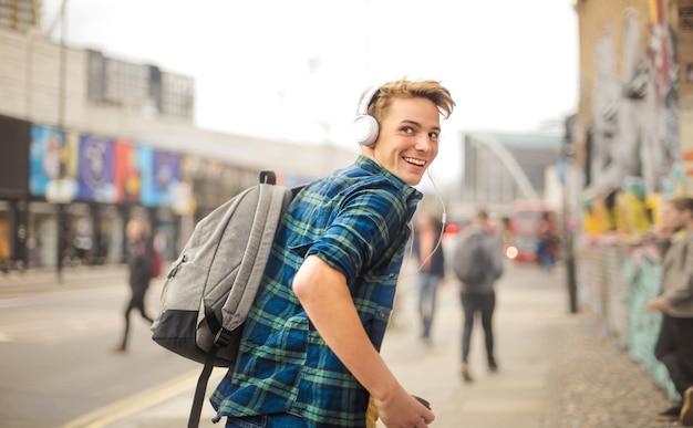 Przystojny facet działa na ulicy podczas słuchania muzyki w słuchawkach
