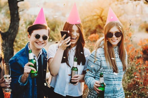 Przystojny facet i ładne kobiety w czapkach imprezowych, uśmiechając się i trzymając butelki piwa, mając imprezę w słoneczny dzień na wsi
