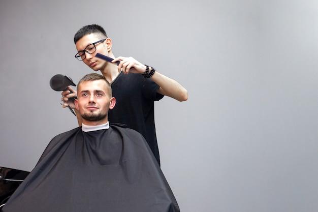 Przystojny facet ma fryzurę w salonie fryzjerskim