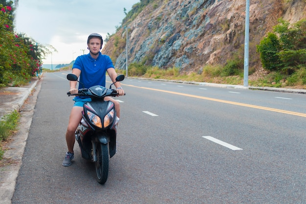Przystojny facet, młody człowiek, rowerzysta lub motocyklista jedzie, jedzie motocyklem, motorowerem lub rowerem w kasku na drodze w górach w letni dzień w azji, wietnam