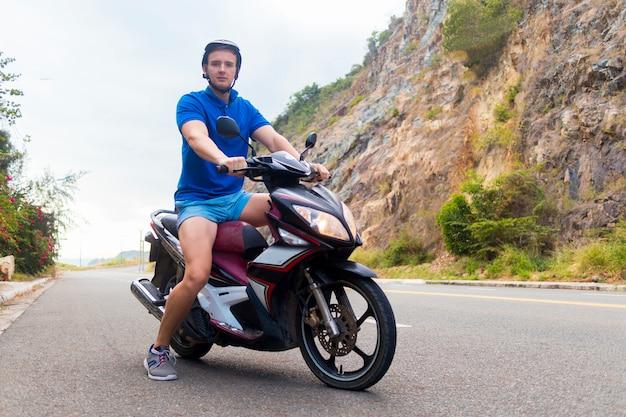 Przystojny facet, młody człowiek, rowerzysta lub motocyklista jedzie, jeździ motocyklem, motorowerem lub rowerem,. jeździec w hełmie na drodze w górach w letnim dniu w azja, wietnam